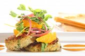 stock photo of crab-cakes  - Gourmet crab cakes with grapefruit slices - JPG
