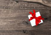 White Gift Box With Red Ribbon Bow On Wooden Background