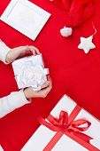 Giftboxes, Santa cap, picture of snowflake and decorative toy star over red background