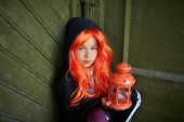 Portrait of Halloween girl holding lantern with candle and looking at camera