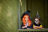 stock photo of youngster  - Portrait of two Halloween girls in costumes looking at camera - JPG