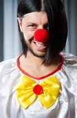 Sad clown against grey background