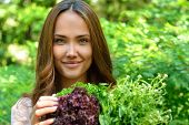 Beautiful slender girl holding healthy fresh greens.