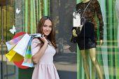 Beautiful young fashion woman holding shopping bags and standing near shop window