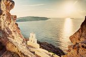 Cliff, volcanic rocks and a traditional chapel on Santorini island, Greece. View on Caldera and Aege