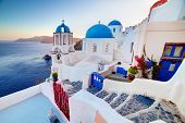 Oia town on Santorini island, Greece at sunset. Traditional and famous churches with blue domes over