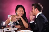 Man Whispering In Woman's Ear At Restaurant