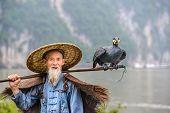 Cormorant fisherman and his bird on the Li River in Yangshuo, Guangxi, China.
