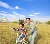 Happy Father Teaching Little Girl To Ride Bicycle