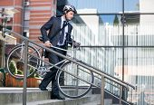 young businessman in crash helmet carrying bicycle down steps