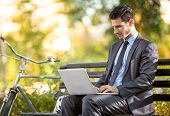 image of work bench  - Businessman with bicycle working on laptop on bench in park - JPG