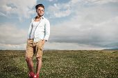 Full body picture of a young man posing in a field full of flowers, looking away with his hands in his pockets.