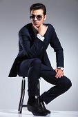 Full body picture of a young elegant business man sitting on a stool holding his hand to his chin, thinking.