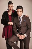 Gorgeous fashion woman standing next to her boyfriend while he is sitting on a stool.