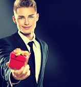 Young handsome man giving red gift box. Elegant businessman in dark suit over black background. Sexy blonde smiling guy with holiday Valentine's Day gift