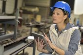 stock photo of mechanical engineering  - Woman engineer in steel plant using tablet - JPG