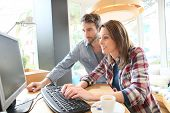 Couple in coffee shop websurfing on desktop computer