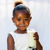 Cute African Girl Drinking Glass Of Milk.