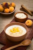 stock photo of peach  - Bowl of oatmeal porridge served with peach slices photographed with natural light  - JPG