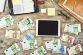 Office supplies, gadgets and money on wooden table