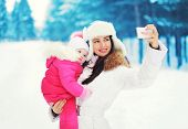 Beautiful Mother And Child Makes Photo Self-portrait On The Smartphone In The Winter Day