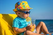 image of fruit-juice  - Amusing kid drinks juice from tubule against sea in sunny day - JPG