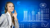 Businesswoman in headset. Skyscrapers beside, hi-tech graphs with various data as backdrop