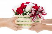 stock photo of gift basket  - Hand delivers baskets of red and white rose flowers as a gift isolated on white background - JPG