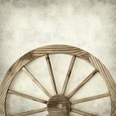 foto of wagon wheel  - textured old paper background with old wagon wheel - JPG