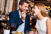 pic of heterosexual couple  - Beautiful young loving couple enjoying dinner at the restaurant while man feeding his girlfriend with salad - JPG