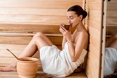 image of sauna  - Young woman in white towel drinking tea sitting in Finnish sauna - JPG