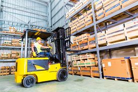 stock photo of warehouse  - Asian fork lift truck driver lifting pallet in storage warehouse - JPG