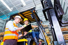 stock photo of warehouse  - Asian fork lift truck driver discussing checklist with foreman in warehouse  - JPG