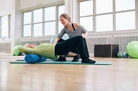 stock photo of pilates  - Female trainer instructing senior woman going exercise on a foam roller - JPG