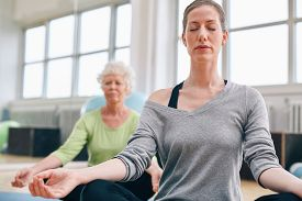 stock photo of senior class  - Mature woman doing yoga with senior female in background - JPG