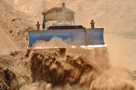 picture of bulldozers  - A small bulldozer works to remove top soil and duft with organic material from a new commercial development project - JPG