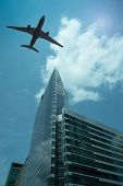 stock photo of noise pollution  - Airplane in the sky with modern buildings - JPG