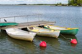 stock photo of dock  - Three rowboats at wooden dock with buoy waiting for customers - JPG