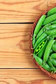 pic of pea  - Fresh green peas pods in a basket on the red wooden table - JPG