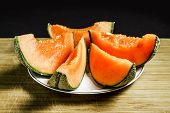 stock photo of cantaloupe  - Slices of succulent orange cantaloupe melon on a plate