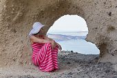 stock photo of cave woman  - Woman in a long dress sitting on rocks of cliff near cave in the shape of a heart - JPG