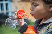 pic of kiddie  - Child inflating the soap bubbles at summer outside - JPG