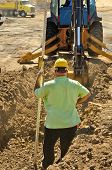 foto of street-rod  - Construction excavation contractor uses a level rod and laser to dig a trench for a concrete fondation wall - JPG