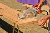 stock photo of worm  - Building contractor worker using hand held worm drive circular saw to cut boards on a new home construciton project - JPG