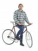 stock photo of bicycle gear  - Young man doing tricks on fixed gear bicycle on a white background - JPG