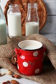 picture of caw  - Milk in glassware and walnuts on wooden table with sackcloth - JPG