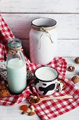 image of caw  - Milk in glassware with walnuts and cookies on wooden table with napkin - JPG
