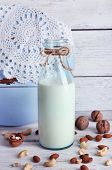 pic of caw  - Milk in glassware and walnuts on wooden background - JPG