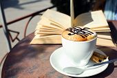pic of treble clef  - Cups of cappuccino with treble clef on foam  and book on table in cafe - JPG