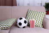 stock photo of comfort  - Soccer ball and box of popcorn on comfortable sofa - JPG